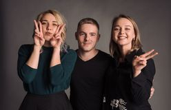 Tre giovani amici che stanno insieme, abbraccianti, ridenti e sorridenti Lo studio sparato nella parete grigia Fotografia Stock