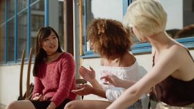 Tre giovani amici femminili al caffè all'aperto archivi video