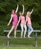 Tre giovani amici femminili che stanno su un banco, all'aperto Fotografie Stock Libere da Diritti