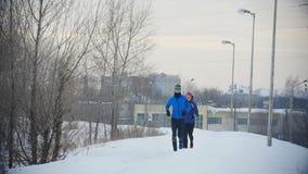 Tre giovani atleti che corrono nell'inverno all'aperto stock footage