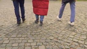 Tre giovani che camminano sulle pietre dei lastricatori stock footage