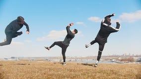 Tre giovani che eseguono contemporaneamente i trucchi acrobatici sull'erba stock footage