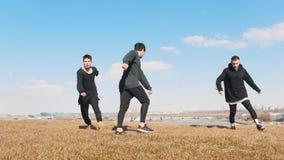 Tre giovani che eseguono contemporaneamente vibrazione acrobatica sull'erba archivi video