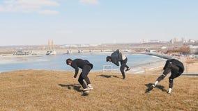 Tre giovani che fanno contemporaneamente i trucchi acrobatici sull'erba stock footage