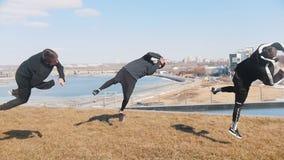 Tre giovani che fanno i trucchi acrobatici sull'erba archivi video