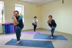 Tre giovani che fanno yoga allo studio di forma fisica Fotografia Stock Libera da Diritti