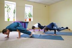 Tre giovani che fanno yoga allo studio di forma fisica Fotografie Stock Libere da Diritti
