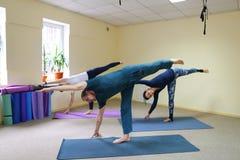 Tre giovani che fanno yoga allo studio di forma fisica Fotografie Stock