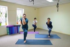 Tre giovani che fanno yoga allo studio di forma fisica Immagini Stock