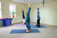 Tre giovani che fanno yoga allo studio di forma fisica Fotografia Stock