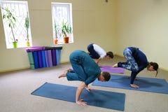 Tre giovani che fanno yoga allo studio di forma fisica Immagine Stock Libera da Diritti