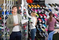 Tre giovani che mostrano un assortimento di scarpe nella st Immagine Stock Libera da Diritti