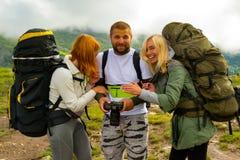 Tre giovani degli amici dei turisti: un tipo e un blon di due ragazze immagine stock