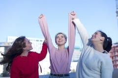 Tre giovani donne adulte emozionanti felici in abbigliamento casual celebrano l'aria aperta di vittoria fotografie stock libere da diritti