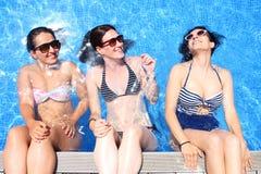 Tre giovani donne allegre simulano che si siedono sopra il bordo di uno stagno con una parete dell'acqua indietro Fotografia Stock