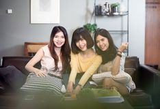 Tre giovani donne asiatiche d'avanguardia chegodono della seduta sorridente e dell'esame della macchina fotografica Fotografia Stock