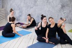 Tre giovani donne che fanno selfie dopo l'allenamento alla classe di yoga immagini stock