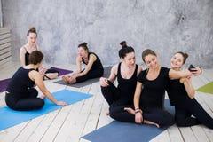Tre giovani donne che fanno selfie dopo l'allenamento alla classe di yoga fotografie stock