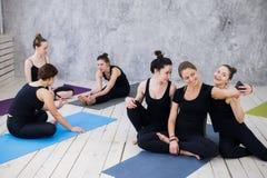 Tre giovani donne che fanno selfie dopo l'allenamento alla classe di yoga fotografie stock libere da diritti