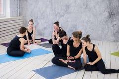 Tre giovani donne che fanno selfie dopo l'allenamento alla classe di yoga immagine stock