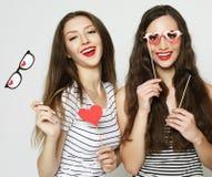 Tre giovani donne che tengono i bastoni di carta del partito fotografie stock