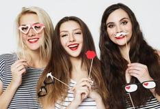 Tre giovani donne che tengono i bastoni di carta del partito immagine stock libera da diritti