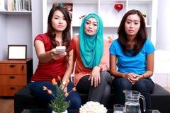 Tre giovani donne con le espressioni piane del fronte quando guardano telev immagine stock