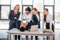 Tre giovani donne di affari arrabbiate che puniscono uomo d'affari che si trova sulla tavola Fotografia Stock