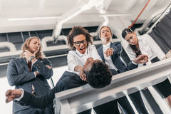Tre giovani donne di affari arrabbiate che puniscono uomo d'affari che si trova sulla tavola Fotografie Stock Libere da Diritti