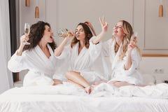Tre giovani donne europee 20s divertendosi all'addio al nubilato ed alla bevanda fotografia stock