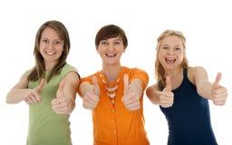 Tre giovani donne felici che danno i pollici in su Fotografia Stock