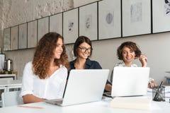 Tre giovani donne felici che lavorano dalla tavola Fotografia Stock