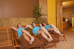 Tre giovani donne sui loungers davanti a sauna fotografia stock libera da diritti