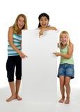 Tre giovani femmine con la scheda bianca Fotografie Stock Libere da Diritti