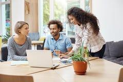 Tre giovani imprenditori futuri che si siedono alla biblioteca, discutendo i business plan ed i profitti del ` s della società, f immagine stock libera da diritti