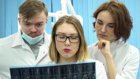 Tre giovani medici che guardano in pieno immagine radiografica dei raggi x del corpo, ricerca di ct, mri sul fondo del gabinetto  archivi video