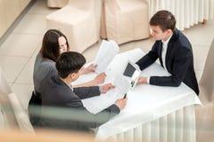 Tre giovani persone di affari che si siedono in una riunione alla tavola e Fotografia Stock