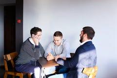 Tre giovani programmatori maschii comunicano per mezzo della compressa mentre sitt Fotografia Stock Libera da Diritti