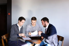 Tre giovani programmatori maschii comunicano per mezzo della compressa mentre sitt Immagini Stock Libere da Diritti