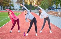 Tre giovani ragazze di sport che fanno ginnastica di mattina sull'erba verde aria aperta, alba, forma fisica, salute, sport Fotografia Stock