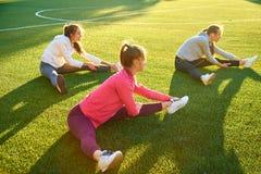 Tre giovani ragazze di sport che fanno ginnastica di mattina sull'erba verde aria aperta, alba, forma fisica, salute, sport fotografie stock libere da diritti
