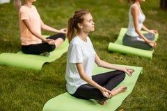 Tre giovani ragazze esili si siedono nelle posizioni di loto con gli occhi di chiusura che fanno l'yoga sulle stuoie di yoga su e fotografia stock