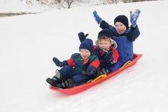 Tre giovani ragazzi che sledding insieme in discesa Fotografia Stock