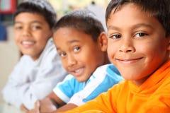 Tre giovani ragazzi di banco primario sorridenti che si siedono dentro Immagini Stock