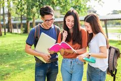 Tre giovani studenti asiatici della città universitaria godono del fischio della lettura e di ripetizioni Fotografia Stock