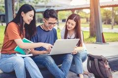 Tre giovani studenti asiatici della città universitaria godono del fischio della lettura e di ripetizioni Fotografie Stock