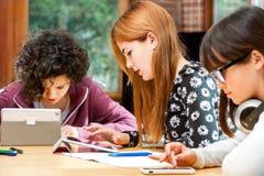 Tre giovani studenti che lavorano ai divices digitali. Immagine Stock