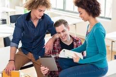 Tre giovani studenti che per mezzo sia di un libro che di un PC della compressa per il controllo delle informazioni Fotografie Stock