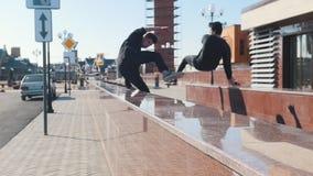 Tre giovani uomini atletici che superano gli ostacoli sulle vie urbane archivi video