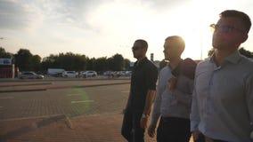 Tre giovani uomini d'affari che camminano nella città con il chiarore del sole al fondo Uomini di affari che permutano per lavora stock footage